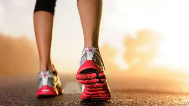 Runner feet running on road closeup on shoe - Winning is a habit